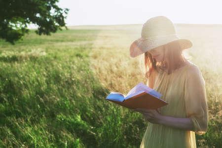 Pretty woman in hat reading book in summer sunlight