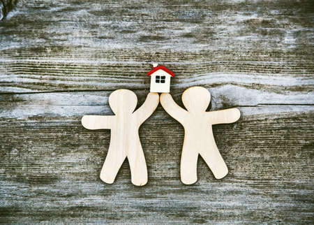 Little men holding house on wooden background. Symbol of construction, family. Sweet home concept