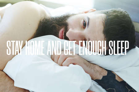 Bearded man lying in morning bed with text Stay home and get enough sleep. Home isolation and quarantine during coronavirus covid-19 pandemic. Imagens