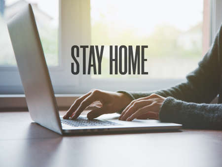 Home office with freelancer hands with laptop and text Stay home. Home isolation and quarantine during coronavirus covid-19 pandemic.