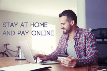 Man holding credit card making online shopping with text Stay home and pay online. Home isolation and quarantine during coronavirus covid-19 pandemic.