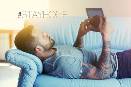 Home office with freelancer lying in sofa with tablet and text Stay home. Home isolation and quarantine during coronavirus covid-19 pandemic. Imagens