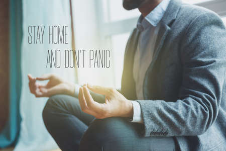 businessman doing yoga in lotus pose with text Stay home and don't panic. Home isolation and quarantine during coronavirus covid-19 pandemic.