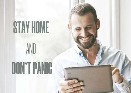 smiling businessman holding digital tablet with text Stay home and don't panic. Home isolation and quarantine during coronavirus covid-19 pandemic.