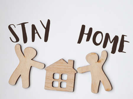 Little wooden men and house with text Stay home. Home isolation and quarantine during coronavirus covid-19 pandemic.