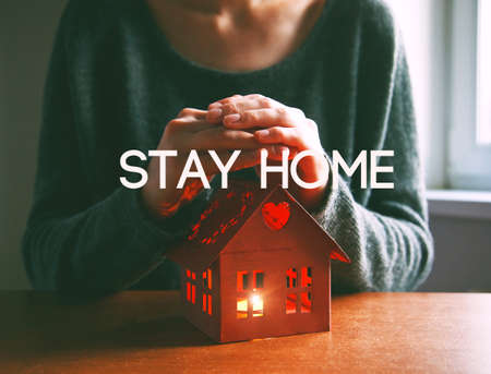 Hands protecting house with candle with text Stay home. Home isolation and quarantine during coronavirus covid-19 pandemic.