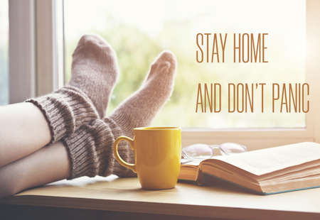 Woman resting keeping legs in warm socks on table with coffee and book with text Stay home and don't panic. Home isolation and quarantine during coronavirus covid-19 pandemic.