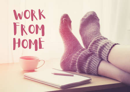 Woman resting keeping legs in socks on table with coffee and text Work from home. Home isolation and quarantine during coronavirus covid-19 pandemic. Imagens