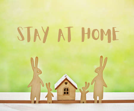 Family of wooden hares near house with text Stay at home. Home isolation and quarantine during coronavirus covid-19 pandemic.