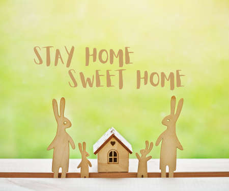 Family of wooden hares near house with text Stay at home sweet home. Home isolation and quarantine during coronavirus covid-19 pandemic. Imagens