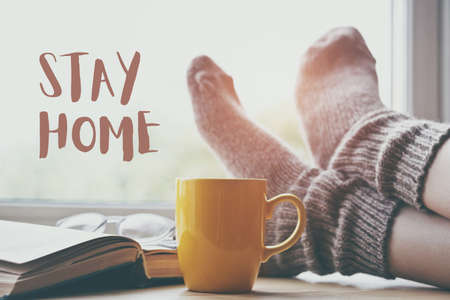 Woman resting keeping legs in socks on table with coffee and book with text Stay home. Home isolation and quarantine during coronavirus covid-19 pandemic.