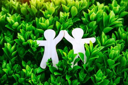 Wooden little men holding hands. Teamwork, environment and ecology concept Imagens