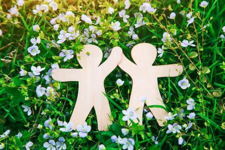 Wooden little men holding hands. Love, environment and ecology concept Imagens