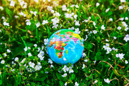 Planet earth model in green grass. Ecology, atmosphere and environment concept.