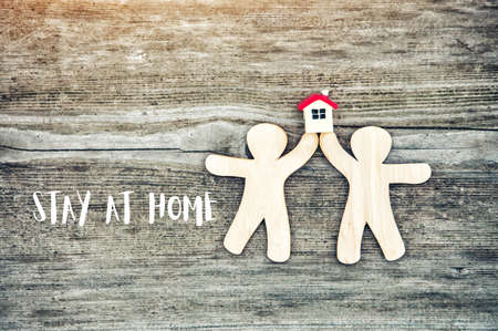 Toy little men holding house model with Stay at home text. Coronavirus prevention, quarantine isolation concept.