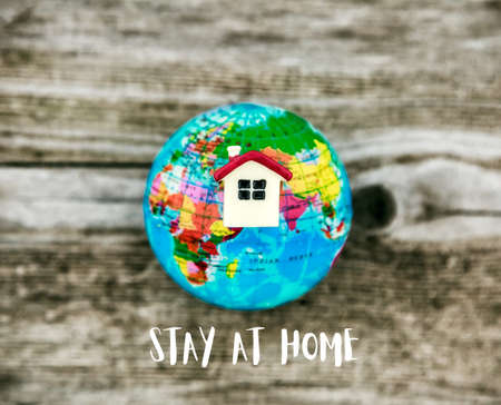 House and globe model with Stay at home text. Coronavirus prevention, quarantine isolation concept.