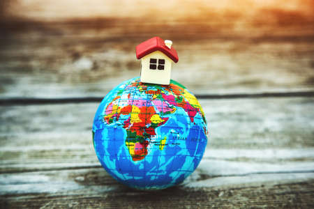 Little toy house on earth planet model. Motherland, ecology, property concept. Symbol of home Imagens