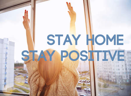 Woman raising hands at morning and text Stay home stay positive. Home isolation and quarantine during coronavirus covid-19 pandemic.