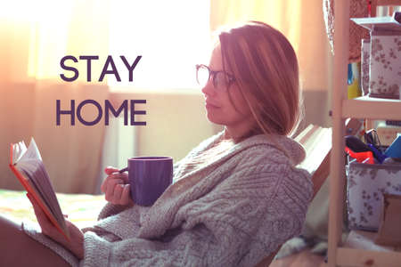 Pretty girl reading book with coffee and text Stay home. Home isolation and quarantine during coronavirus covid-19 pandemic. Stock Photo