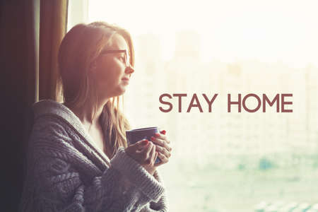 Pretty girl drinking coffee in morning and text Stay home. Home isolation and quarantine during coronavirus covid-19 pandemic.