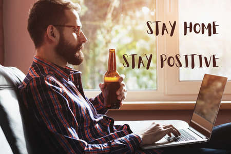 bearded man with laptop drinking bottle of beer and text Stay home stay positive. Home isolation and quarantine during coronavirus covid-19 pandemic.
