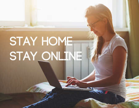 Woman with laptop sitting on bed in morning and text Stay home stay online. Home isolation and quarantine during coronavirus covid-19 pandemic.