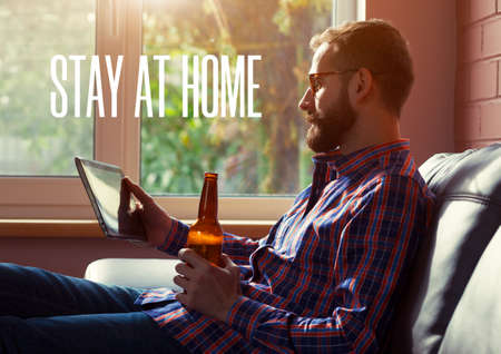 Man with digital tablet drinking beer and text Stay home. Home isolation and quarantine during coronavirus covid-19 pandemic.
