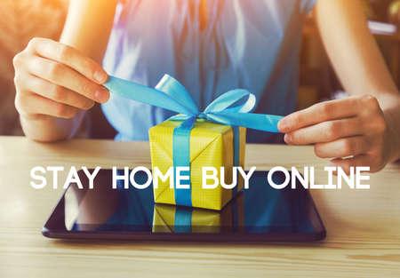 Mains avec coffret cadeau et tablette numérique. Texte Restez chez vous acheter en ligne. Isolement à domicile et quarantaine pendant la pandémie de coronavirus covid-19. Banque d'images