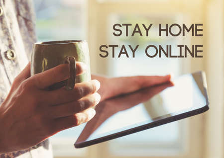 Hands holding digital tablet with coffee and text Stay home stay online. Home isolation and quarantine during coronavirus covid-19 pandemic. Imagens - 146255215