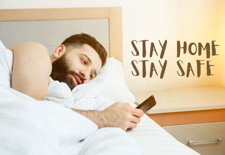 Man lying in morning bed with phone using app or reading news feed and text Stay home stay safe. Home isolation and quarantine during coronavirus covid-19 pandemic.