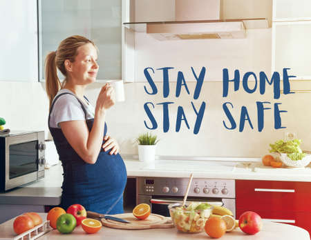Pregnant woman on kitchen drinking juice or tea and text Stay home stay safe. Home isolation and quarantine during coronavirus covid-19 pandemic. Imagens