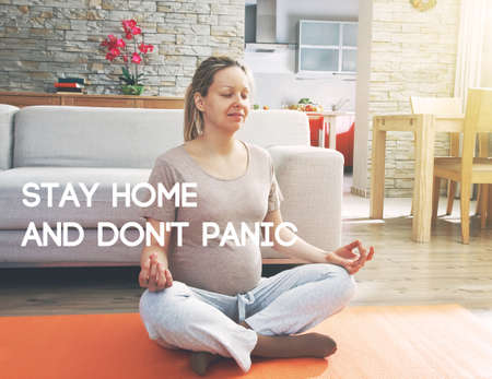 Pregnant woman practicing yoga and relaxing while sitting in lotus position.  Text Stay home and don't panic. Home isolation and quarantine during coronavirus covid-19 pandemic.