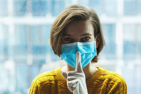 Woman in medical mask with finger near mouth. Panic, silence and calm during coronavirus pandemic concept.