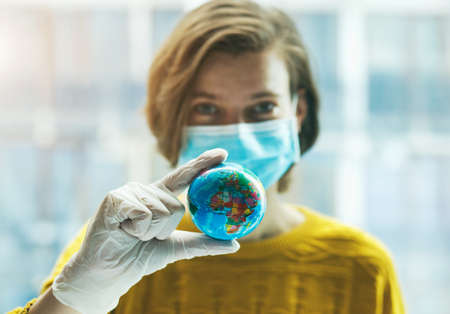Woman in medical mask holding global earth model in hand in gloves. Global problem of coronavirus pandemic concept. Imagens
