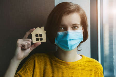 Woman in medical mask holding model go house. Stay at home symbol. Home Isolation during coronavirus pandemic concept. Imagens