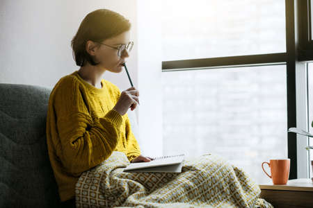 Woman working or studying writing with pencil and notebook at home quarantine. Stay at home campaign.