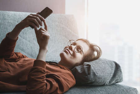 Woman working with phone or feeding social networks at home in morning sunlight. Typing with finger on touch screen lying on cozy couch. Imagens
