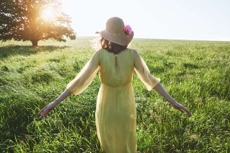 Pretty woman with yellow dress and hat walking in summer field in sunlght