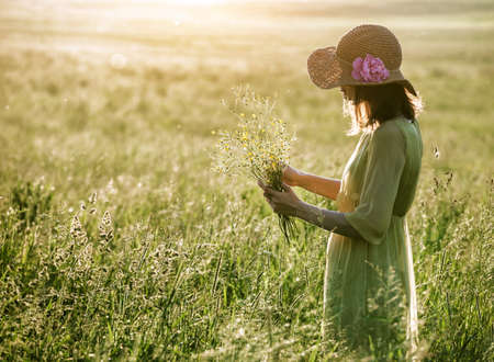 Pretty woman with hat holding grass plant in summer field Imagens - 147702764