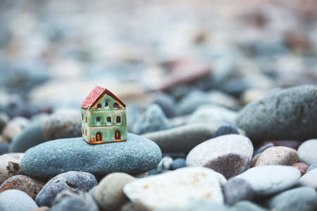 Model of small house in the pebbles stones as symbol with copy space