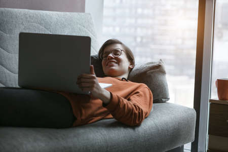 Woman working with laptop at home quarantine. Comfortable workplace lying on couch. Stay at home campaign.