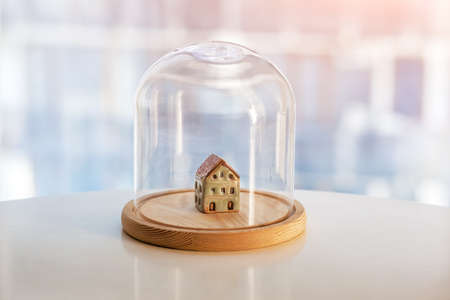 Ceramic model of house under glass cap. Symbol of safe home. Insurance or protecting building property concept. Imagens - 149873274