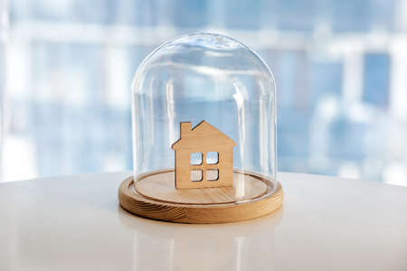 Wooden model of house under glass cap. Symbol of safe home. Insurance or protecting building property concept.