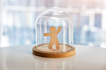 Wooden toy man under glass cap. Protecting life, personality and privacy concept. Symbol of keeping distance during pandemic or life matters