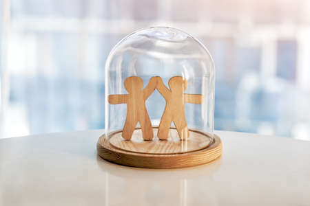 Wooden men under glass cap. Symbol of keeping friendship. Keeping or protecting love concept. Imagens