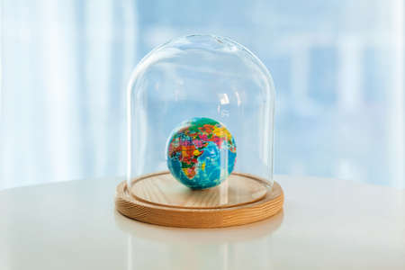 Earth planet model under glass cap. Symbol of keeping nature and ecology. Saving or protecting Earth concept.