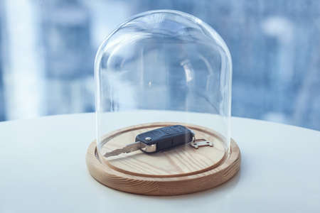 Car key under glass cap. Symbol of car insurance or automobile safety