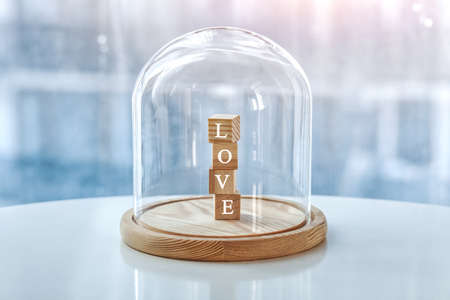 Wooden cubes with Love letters under glass cap. Symbol of keeping love. Saving or protecting love concept.