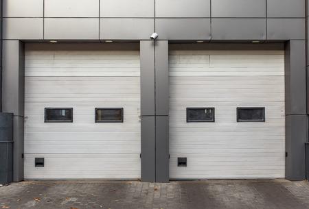 garage doors: Two white garage doors. Sectional lift gates.