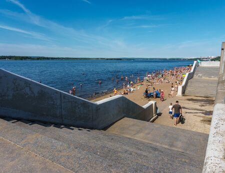 Summer beach on the riverbank with large concrete stairs